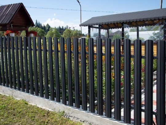 a dark colored and simple aluminium fence built by Hervey Bay Fencing Pros